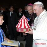 Il Papa osserva divertito il piccolo circo che gli è stato donato da Maicol Martini alla giornata della famiglia